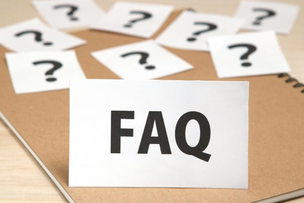 FAQ on a piece of paper and many question marks on notebook. FAQ or Frequently Asked Questions concept.